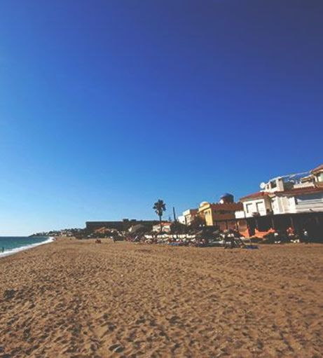Looking down an empty Fuengirola Beach. Discover Fuengirola Stag Party ideas below: