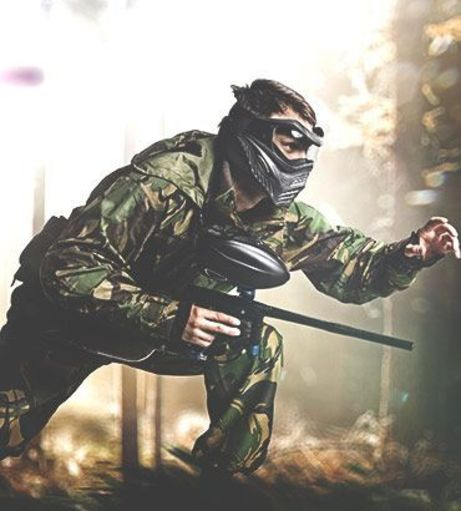 Man in camo kneels down on the ground holding a paintball marker. Get