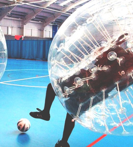 Lad wearing Adidas trainers kicks a football while in a zorb. Get a Li