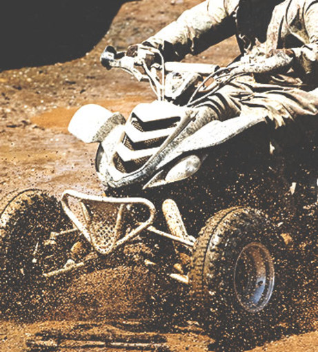 Rider on a quad bike covered in mud. Get a Lincoln Off Road Madness qu
