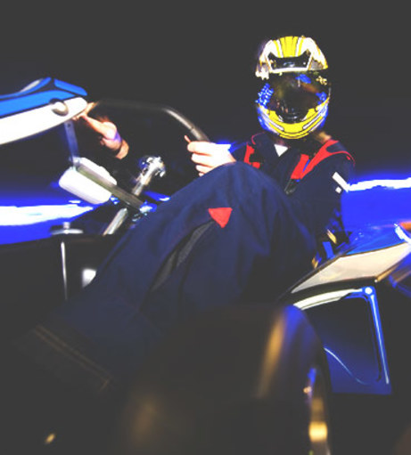Dark image of a kart driver with a helmet on. Get a Lincoln Take to th