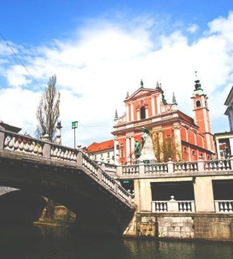 Triple Bridge over Ljubljanica River with a view of the Franciscan Church of the Annunciat