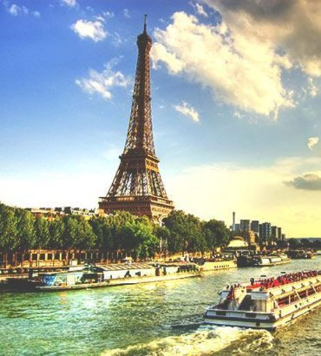 Cloudy skies over the Eiffel Tower and River Seine. Discover Paris Stag Party ideas below: